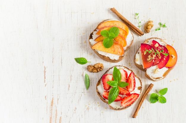 Bruschetta met perziken, pruimen, aardbeien en kwark.