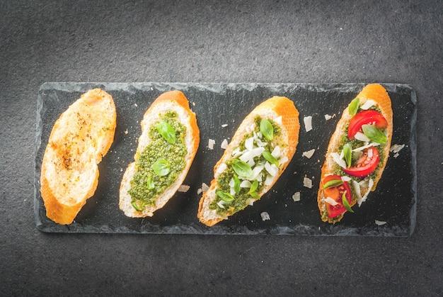 Bruschetta met pesto, parmezaanse kaas, tomaten en basilicum op dienblad