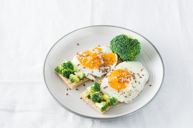 Bruschetta met roerei en broccoli op een korrel knäckebröd op een bord op tafel