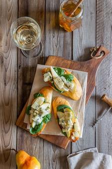 Bruschetta met spinazie, peer en blauwe kaas. wijn. vegetarisch eten. gezond eten. veganisme. eetpatroon.
