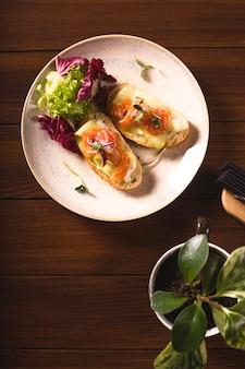 Bruschetta met syomga en komkommer op een bord met groenen.