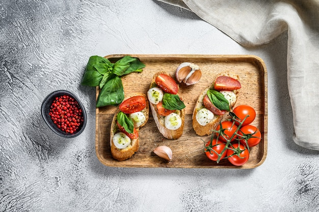 Bruschetta met tomaten, mozzarella kaas en basilicum. italiaans voorgerecht of snack, antipasto. grijze achtergrond. bovenaanzicht