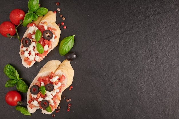 Bruschetta met tomaten, mozzarellakaas en basilicum op een snijplank. traditioneel italiaans voorgerecht of snack, antipasto. caprese salade bruschetta. bovenaanzicht met kopie ruimte. plat leggen.