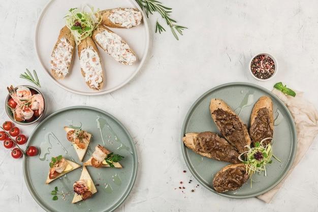 Bruschetta met verschillende toppings van vlees en vis met sauzen op de borden met de stroom van de chef, bovenaanzicht met copyspace. plat leggen. het concept van ontbijt. restaurant eten.