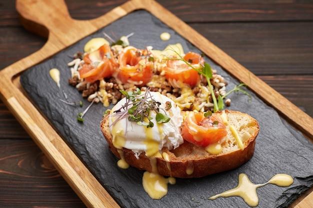 Bruschetta met zalm, gepocheerd ei en kleurstofrijst. op een houten bord