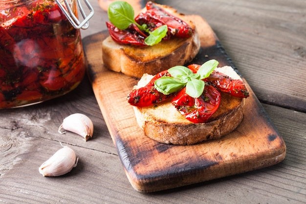 Bruschetta met zongedroogde tomaten, basilicumblaadjes en knoflook