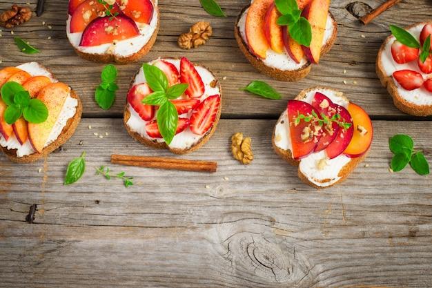 Bruschetta van het de zomerontbijt met pruimen, aardbeien, perziken