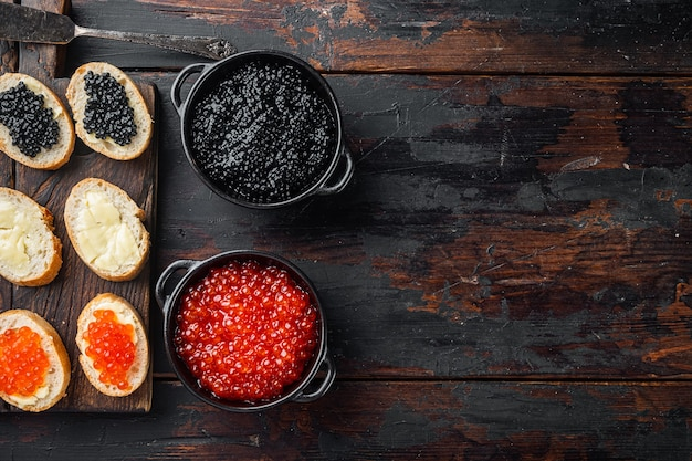 Bruschettes met boter rode en zwarte kaviaar, op oude donkere houten tafel tafel, bovenaanzicht plat lag met kopie ruimte