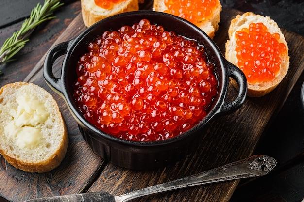 Bruschettes met boter rode kaviaar, op oude donkere houten tafel tafel