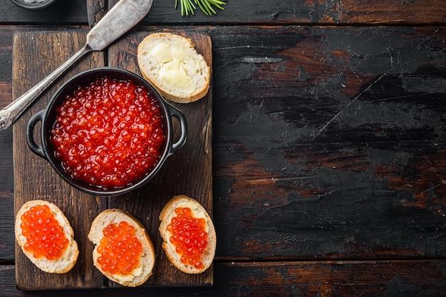 Bruschettes met boter rode kaviaar, op oude donkere houten tafel
