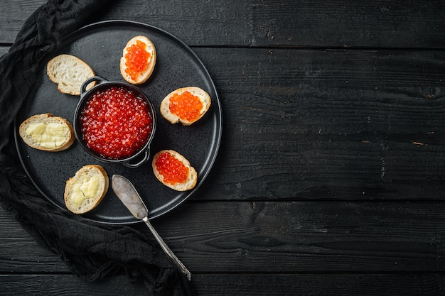 Bruschettes met boter rode kaviaar, op zwarte houten tafel tafel, bovenaanzicht plat lag met kopie ruimte