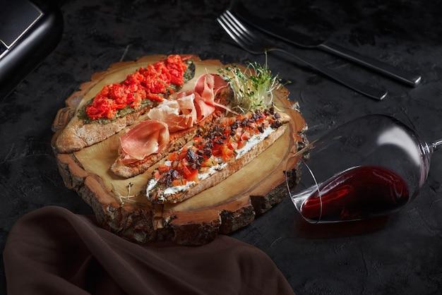 Brushetta set voor wijn. verscheidenheid aan kleine sandwiches met prosciutto, tomaten, parmezaanse kaas, verse basilicum en balsamico crème geserveerd met glas rode wijn op rustieke houten plank op donkere achtergrond