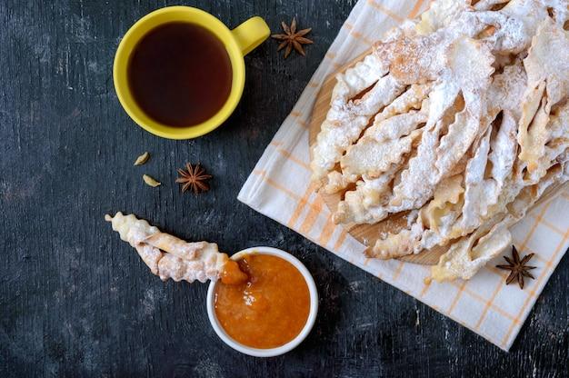 Brushwood crispy gefrituurde koekjes in poedersuiker met thee en jam