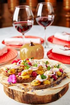 Brusquettes met ei champignons en uien op een houten plank
