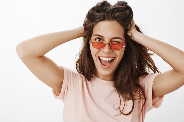 Brutaal aantrekkelijk meisje met zonnebril poseren tegen de witte muur