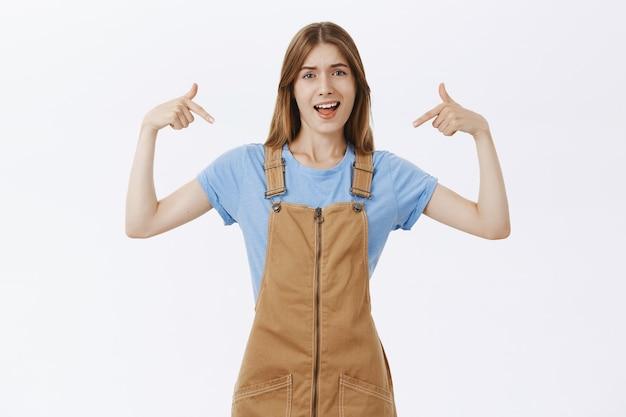 Brutaal aantrekkelijk meisje wijst naar zichzelf of toont logo met zelfverzekerde arrogante uitdrukking