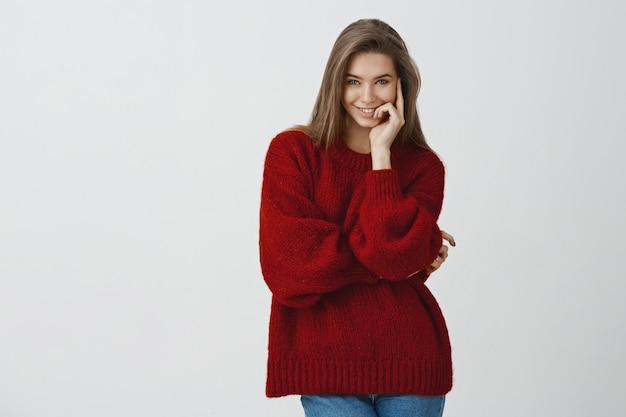 Brutaal en flirterig aantrekkelijk meisje in stijlvolle rode losse wintertrui die lastig en sensueel glimlacht van tevredenheid en vreugde die de lippen met een gerust hart en vertrouwen aanraken