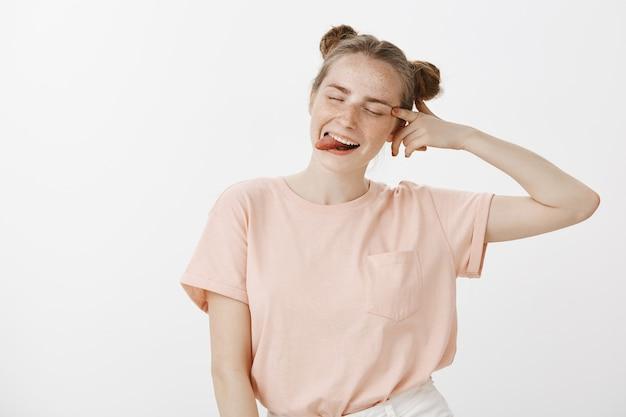 Brutaal en onbezorgd tienermeisje poseren tegen de witte muur