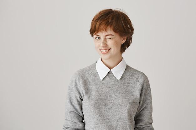 Brutaal glimlachend roodharig meisje met kort kapsel poseren tegen de witte muur