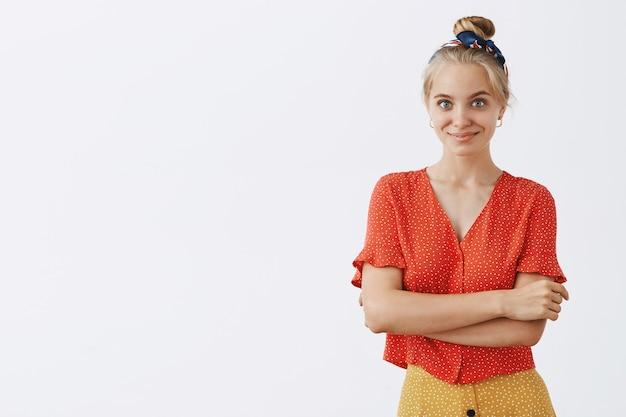 Brutaal jong blond meisje poseren tegen de witte muur