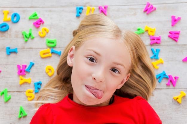 Brutaal klein meisje. bovenaanzicht van een schattig klein meisje dat grijnst terwijl ze op de vloer ligt met plastic kleurrijke letters om haar heen