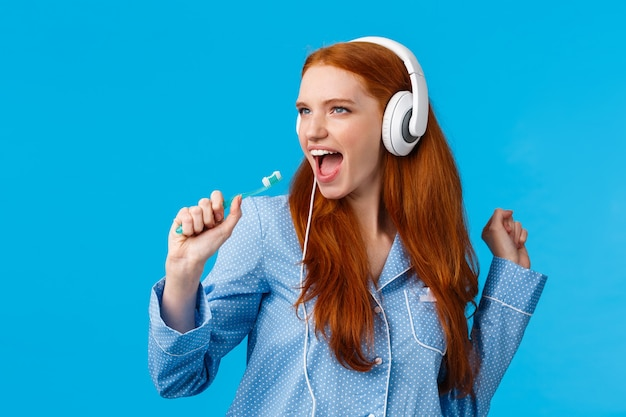 Brutaal knappe roodharige vrouw in pyjama met plezier, muziek luisteren in grote witte koptelefoon