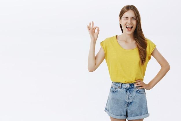 Brutaal lachend meisje dat een goed gebaar toont ter goedkeuring, zoals een idee, garandeert kwaliteit