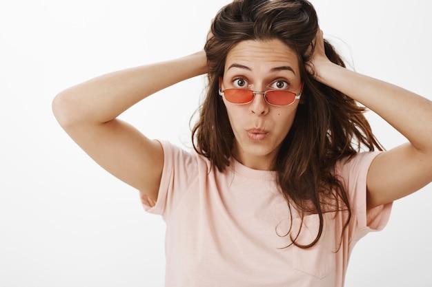 Brutaal meisje met zonnebril poseren tegen de witte muur