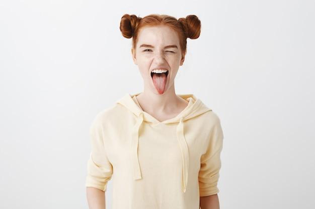 Brutaal roodharig meisje knipoogt en toont tong blij