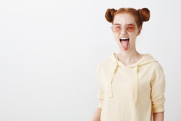 Brutaal roodharigemeisje in modieuze zonnebril die tong toont