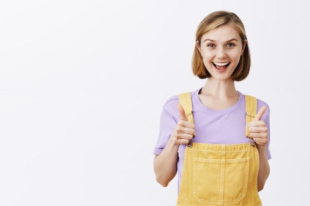 Brutaal schattig blond meisje dat zegt dat je dit hebt, prijs de goede keuze, laat zijn duim omhoog zien en lacht opgetogen