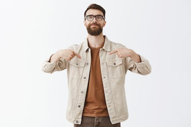 Brutaal tevreden bebaarde man met bril poseren tegen de witte muur