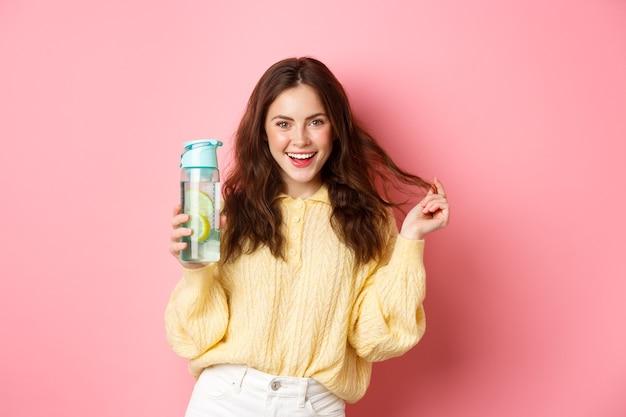 Brutale aantrekkelijke vrouw die zelfverzekerd naar de camera kijkt, persoonlijke fles met citroenwater gezonde drank vasthoudt, staande tegen een roze muur.