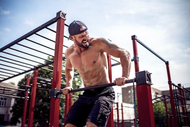Brutale atletische man die pull-up oefeningen op een lat maakt.