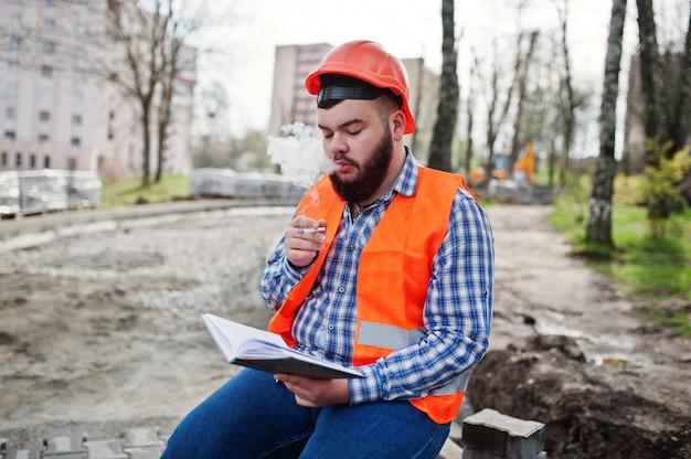 Brutale baard rokende werknemer man pak bouwvakker in oranje veiligheidshelm zittend op de stoep, pauze op het werk, en lees werken notebook ingangen.