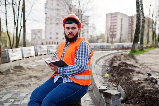 Brutale baard werknemer man pak bouwvakker in oranje veiligheidshelm zittend op de stoep en maakt werken notebook ingangen.