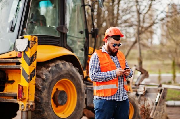 Brutale baard werknemer man pak bouwvakker in veiligheid oranje helm, zonnebril tegen traktor met mobiele telefoon bij de hand.