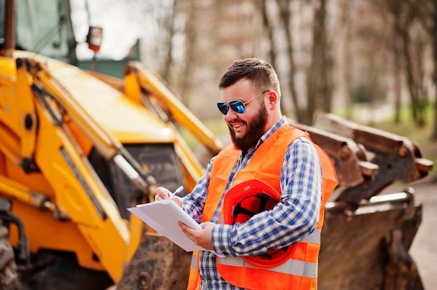 Brutale baard werknemer man pak bouwvakker in veiligheid oranje helm, zonnebril tegen traktor met plan papier op handen.