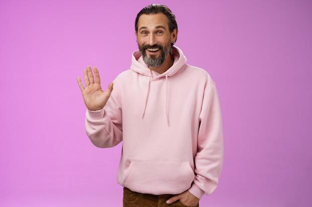 Brutale charismatische grappige gelukkig lachende volwassen man met baard grijs haar in roze hoodie wuivende palm