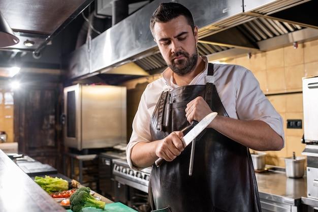 Brutale chef-kok in lederen schort staande op restaurant keuken en mes te scherpen