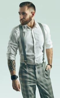 Brutale elegante man in grijze klassieke broek en bretels op wit wordt geïsoleerd
