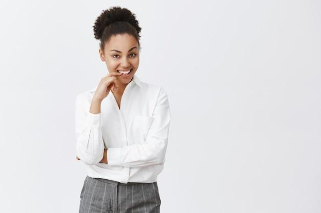 Brutale en doordachte afro-amerikaanse vrouw die lacht tevreden, nadenkend over geweldig bedrijfsidee