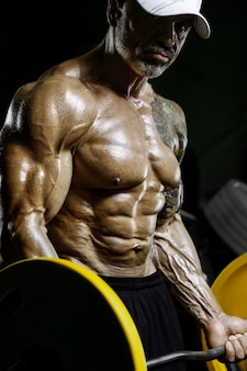 Brutale en gespierde sterke bodybuilder atletische man die spieren oppompt tijdens training in de sportschool