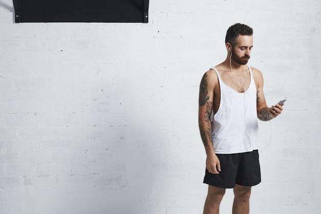 Brutale getatoeëerde atletische man in lege tank t-shirt kijkt in zijn smarthphone, oordopjes dragen voor training op witte bakstenen achtergrond