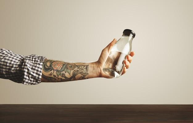 Brutale getatoeëerde hand in gevouwen geruite overhemd houdt transparante glazen fles met schoon drinkwater boven rode houten tafel, geïsoleerd op wit