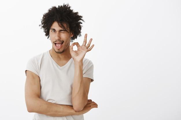 Brutale glimlachende jongeman zegt: geen probleem, goed gedaan. man prijst goede keuze en toont oke gebaar tevreden