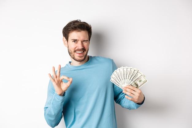 Brutale glimlachende man knipogen, ok teken tonen en geld aanhouden, concept van snelle lening of krediet, staande op een witte achtergrond.
