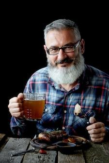 Brutale grijsharige volwassen man met een baard eet mosterdsteak en drinkt bier