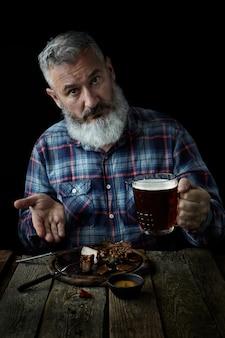 Brutale grijze man met baard eet mosterdsteak en drinkt bier, nodigt uit voor een maaltijd, concept van een vakantie, festival, oktoberfest of st. patrick's day