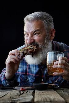 Brutale grijze man met baard eet mosterdsteak en drinkt bier, nodigt uit voor een maaltijd, concept van een vakantie, festival, oktoberfest